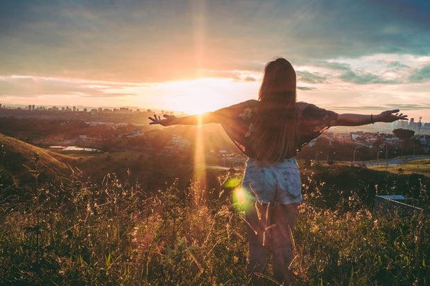 person standing on field facing a sunset