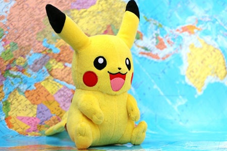 Pikachu (Pokemon) stuffed animal with world map background