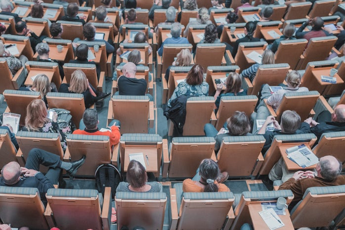 high-angle photo of people seated in a lecture hall