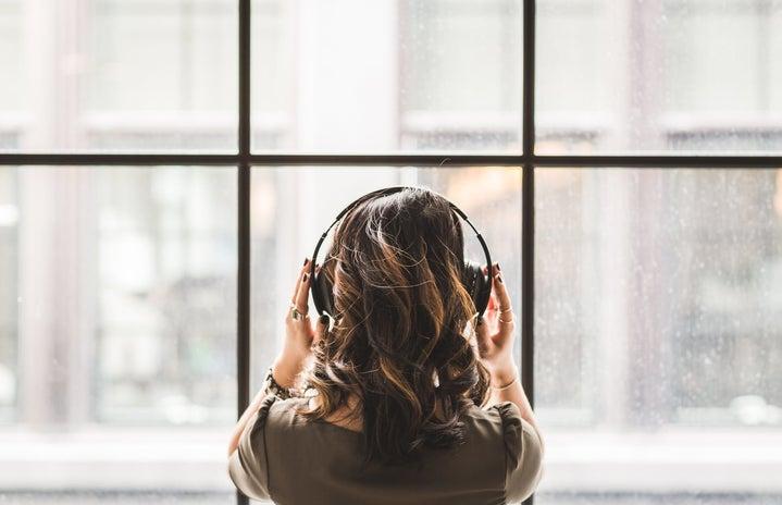 Woman Listening on Headphones Facing a Window