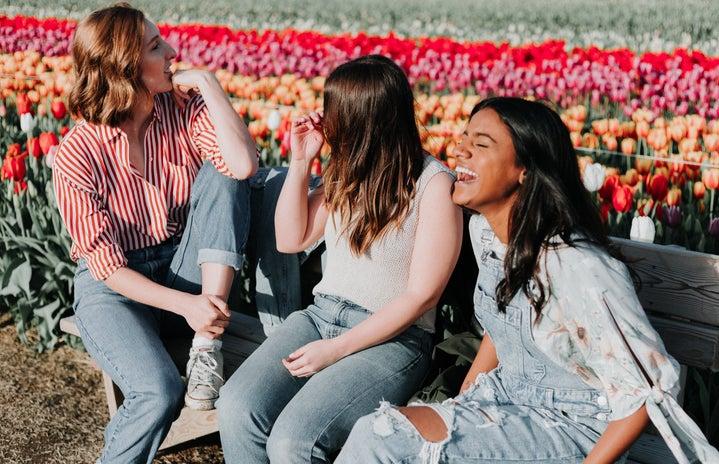three women sitting wooden bench by the tulip flower field