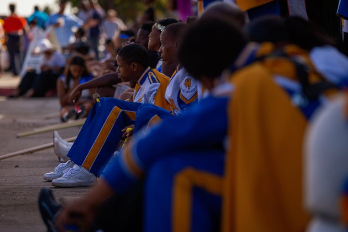 high school marching band sitting on ground