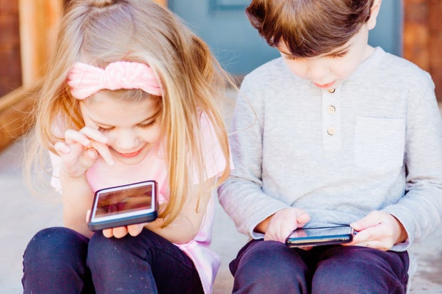 Two children sitting on the steps looking at their phones