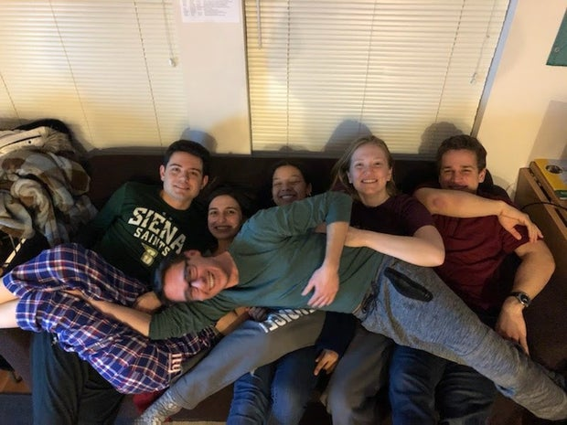 6 friends on couch laughing