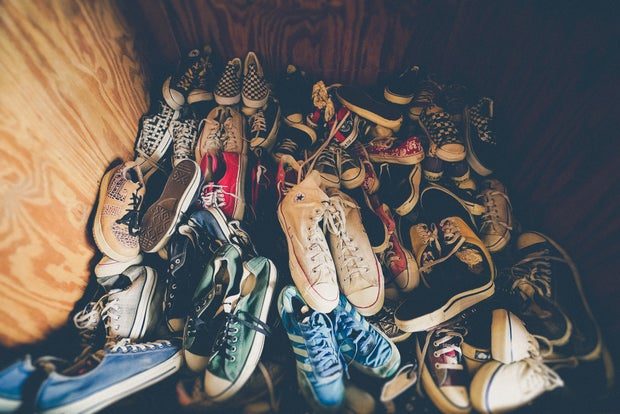 a pile of sneakers, converse and vans sit at the bottom of a closet.