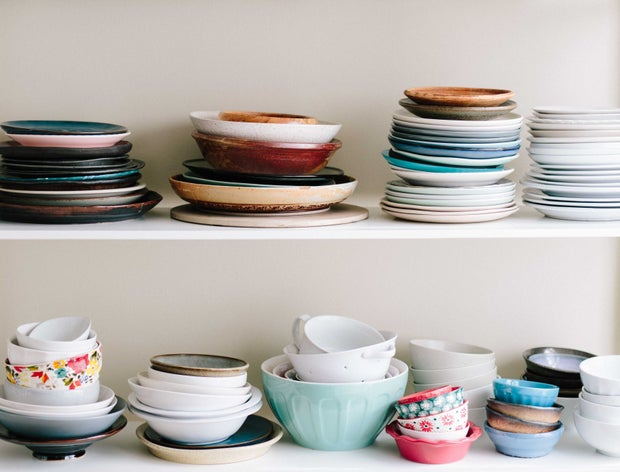 two shelves stacked with plates and bowls of a variety of colors