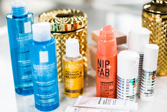 skincare products sit clustered together on a table or vanity