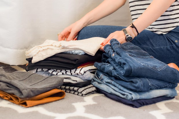 a person sits crosslegged on the ground folding laundry, including jeans and shirts which sit in piles before them