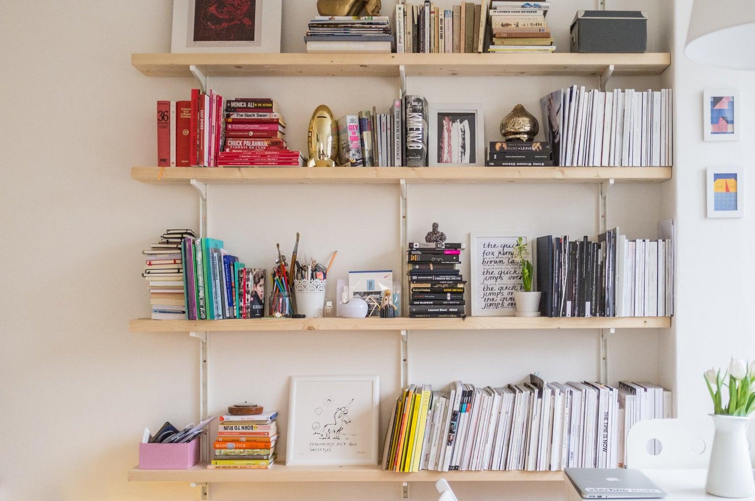 floating wooden shelves full of books, art prints and other knickknacks