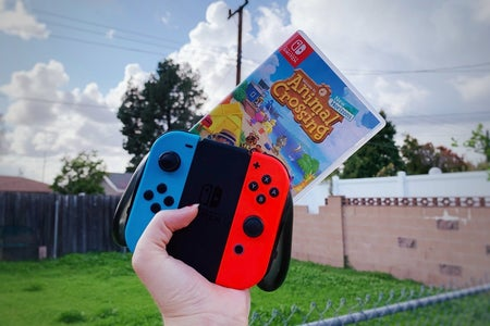 animal crossing game and Nintendo switch controller being held up
