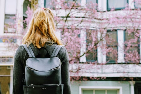 Girl with black backpack standing in front of building
