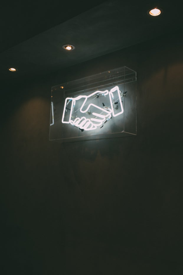 a black and white photo of a neon sign of two hands shaking