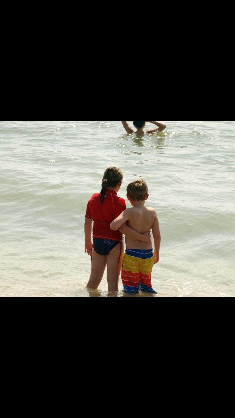 A little boy and girl with arms around each other at the beach