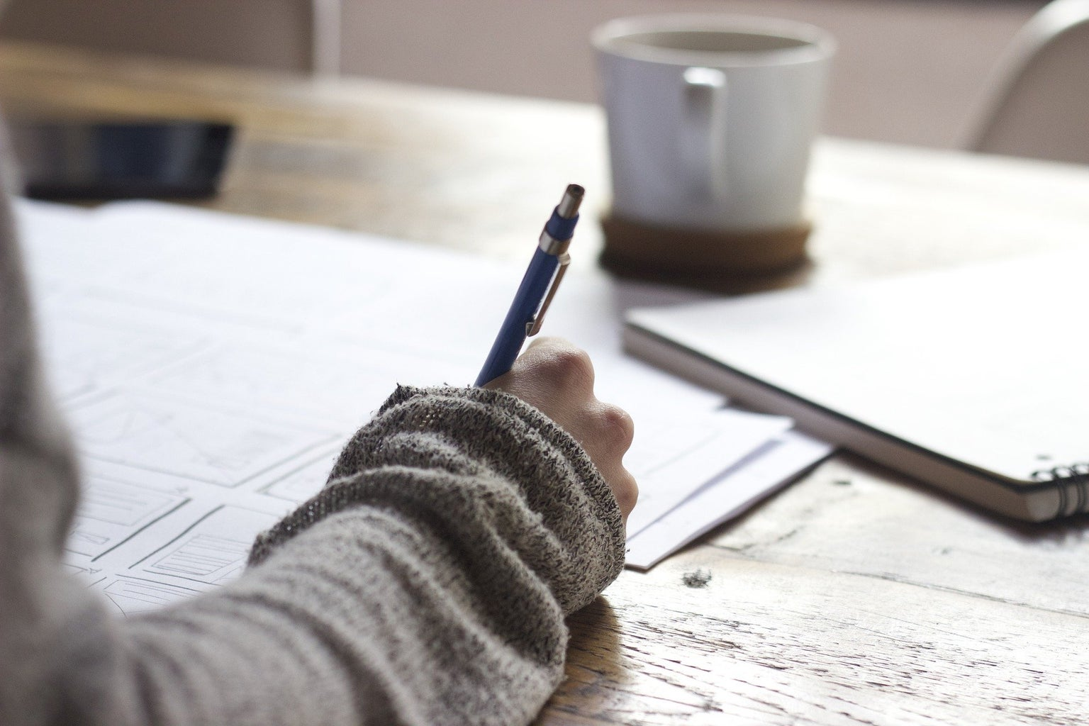 a hand holds a pen writing on sheets of paper on a wooden desk. there's a coffee cup and a notebook in front of it.