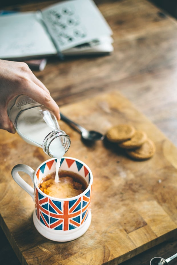 a hand is pouring milk out of a glass bottle into a cup of coffee, which is sitting on a wooden cutting board on a wooden table.