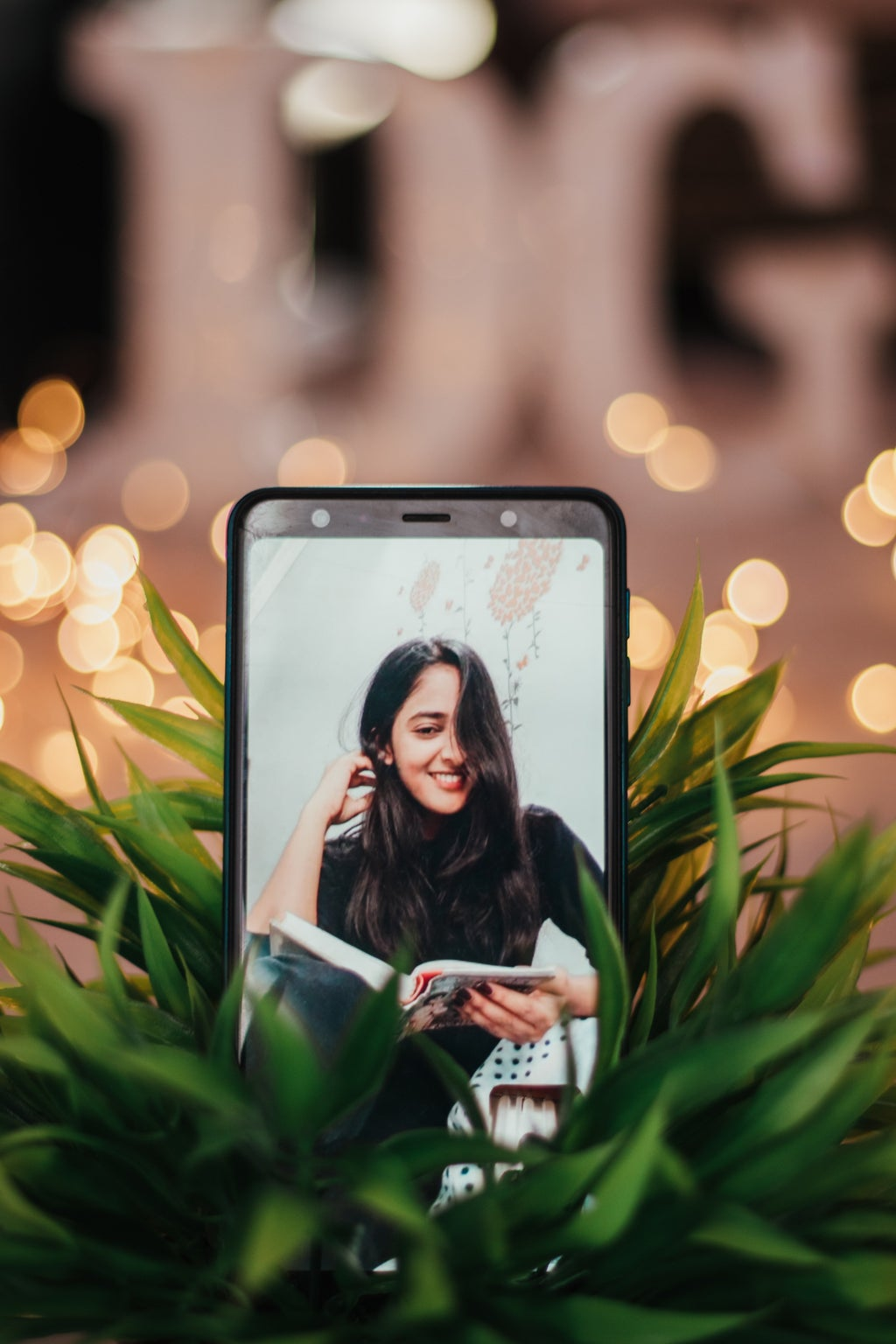 a picture of a picture of a woman on a phone, which is tucked into a plant with fairy lights behind it