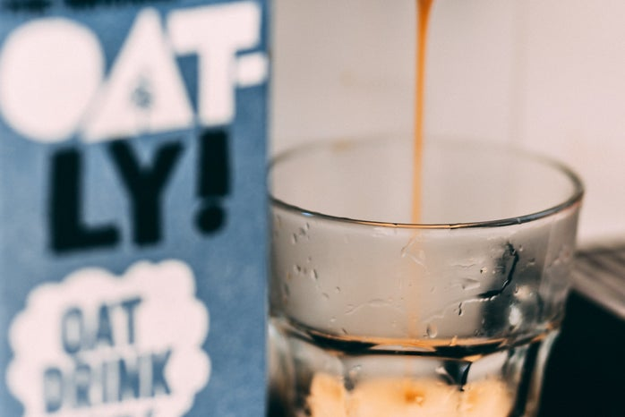 coffee is poured into a glass cup on a counter. there is a carton of oat milk next to it