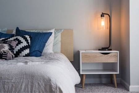 navy and white themed bed with side table