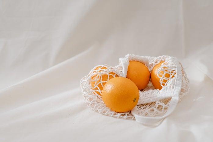 oranges in a white mesh bag