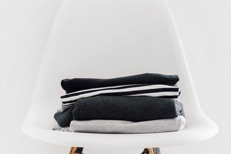 small stack of folded back and white clothing sitting atop a white chair against a white backdrop