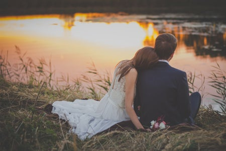 Bride and Groom sitting near a lake