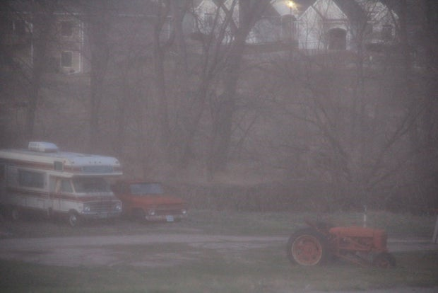 An old tractor and Rv in a farmhouse's front yard.