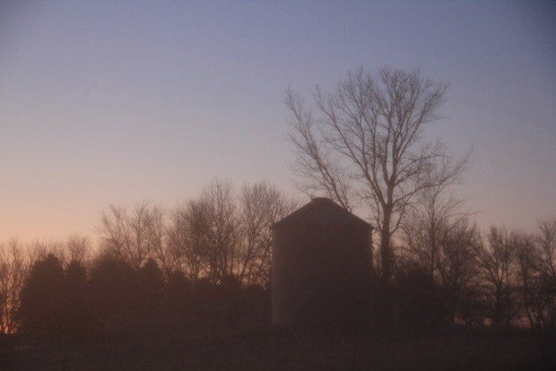 Silhouette of a farm at sunset.