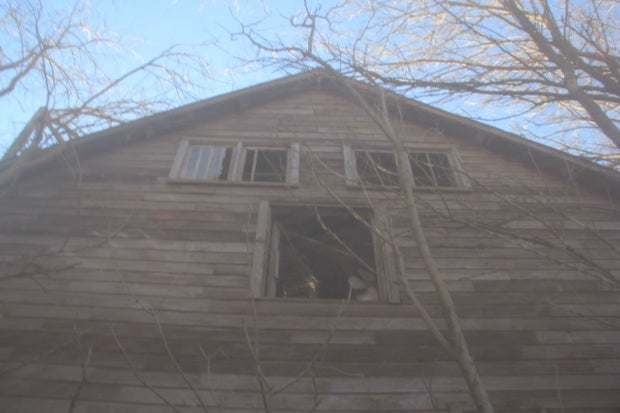 A view of the top of an old brown barn.
