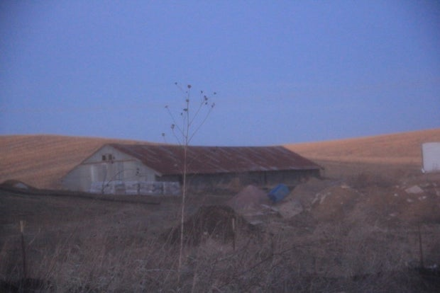 A long agriculture building at dusk.