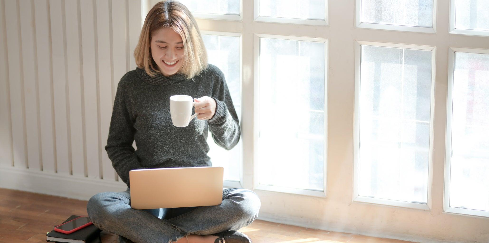 Woman in Grey Sweater holding Coffee Mug