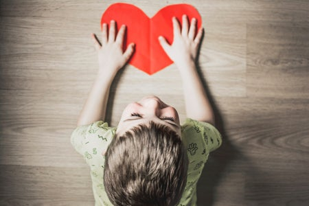 Little boy with paper red heart