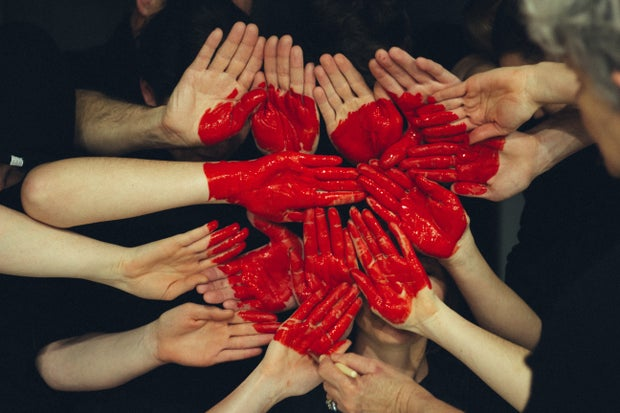 a bunch of hands with red paint on them forming a heart