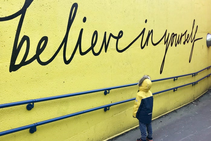 child looking up at inspirational quote on a mural