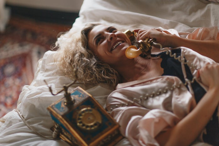 woman on bed making a phone call