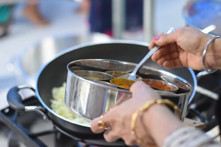 a woman cooking Indian food