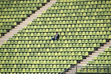 empty stadium seats with one person