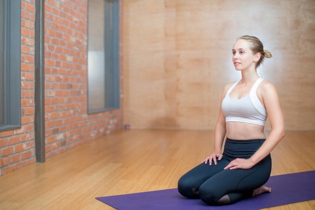 a woman kneeling on a yoga mat