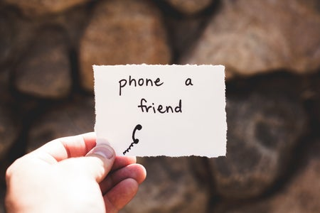 person holding piece of paper with phone a friend written text, mental health
