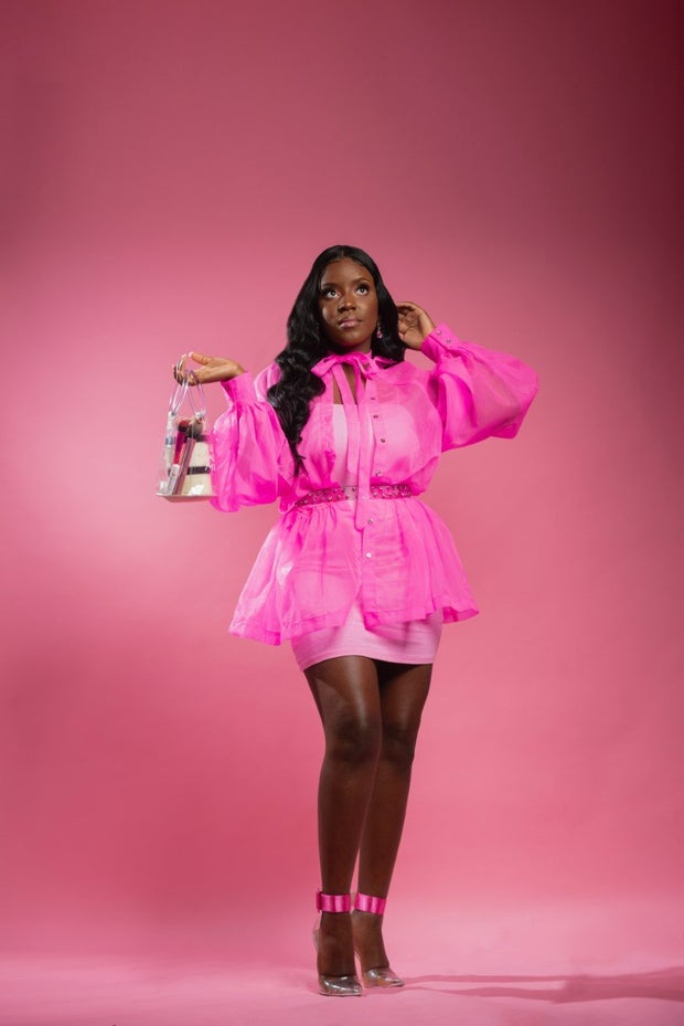A black girl in all pink with a pink background standing up holding an object