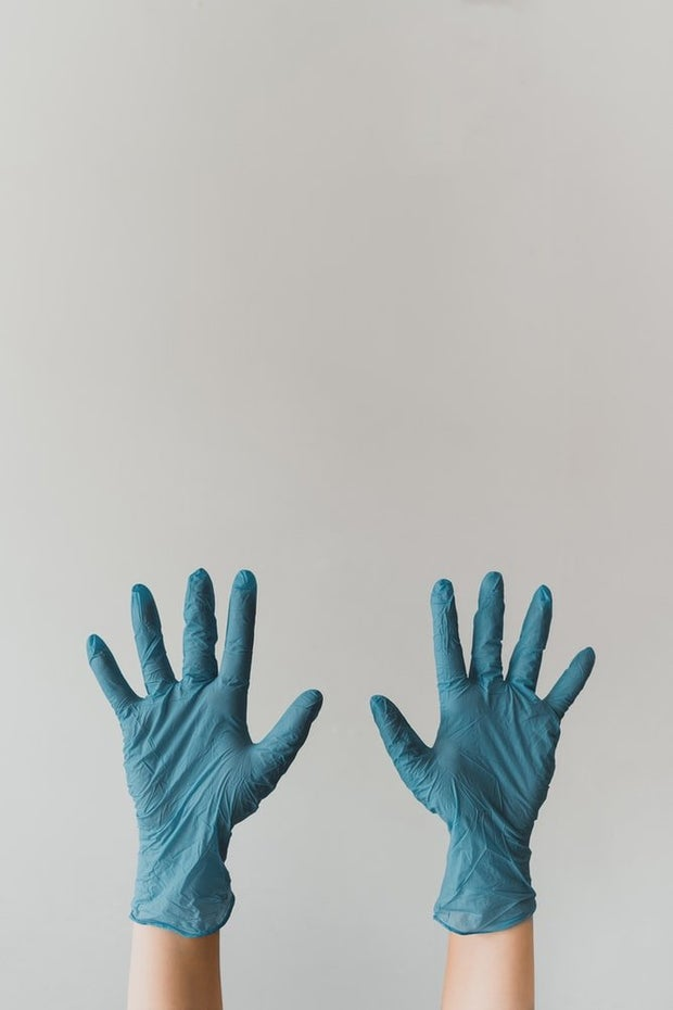Two hands covered by blue gloves rising up into the air