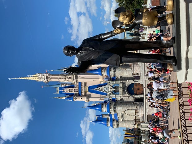 Walt Disney and Mickey Mouse Statue in front of Cinderella's castle at Disney World in Orlando, Florida