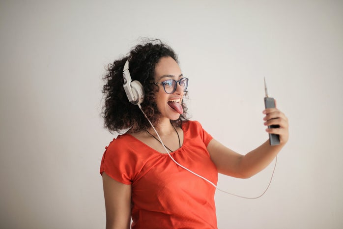 person wearing headphones taking selfie on smartphone