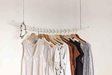 Clothes hanging up on a white rod against a wall