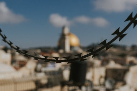 A string of barbed wire in front of the Dome of the Rock