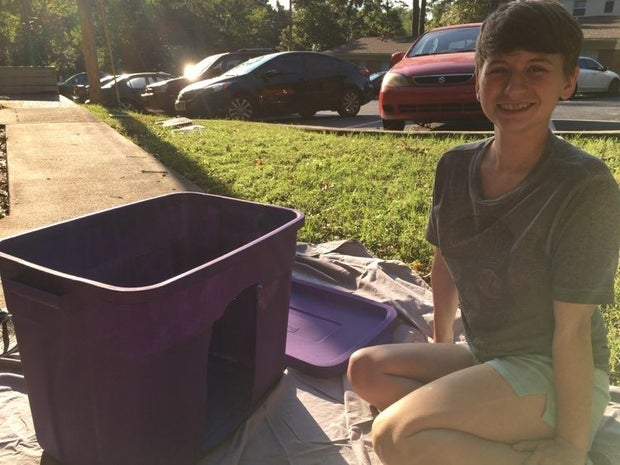 Lindsey sits outside while painting a storage container