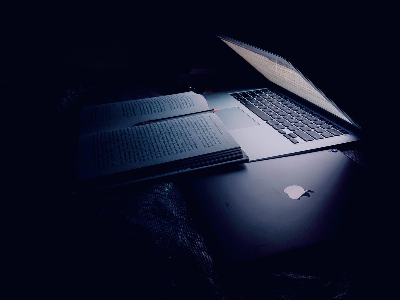 Half closed laptop over book