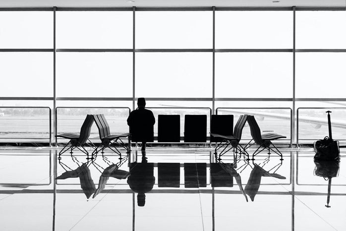 silhouette of person sitting alone in airport waiting area