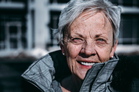 an older woman smiles brightly at the camera. she's outside.