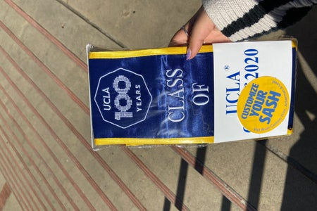 hand holding a ucla class of 2020 sash inside packaging
