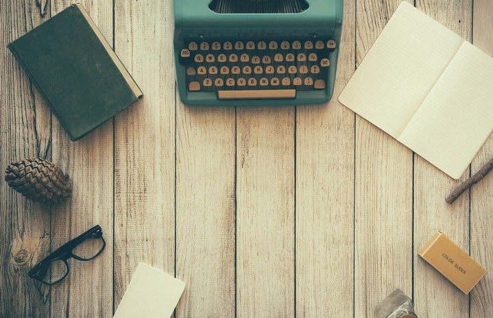 flat lay of a wooden desk with a typewriter and notebooks